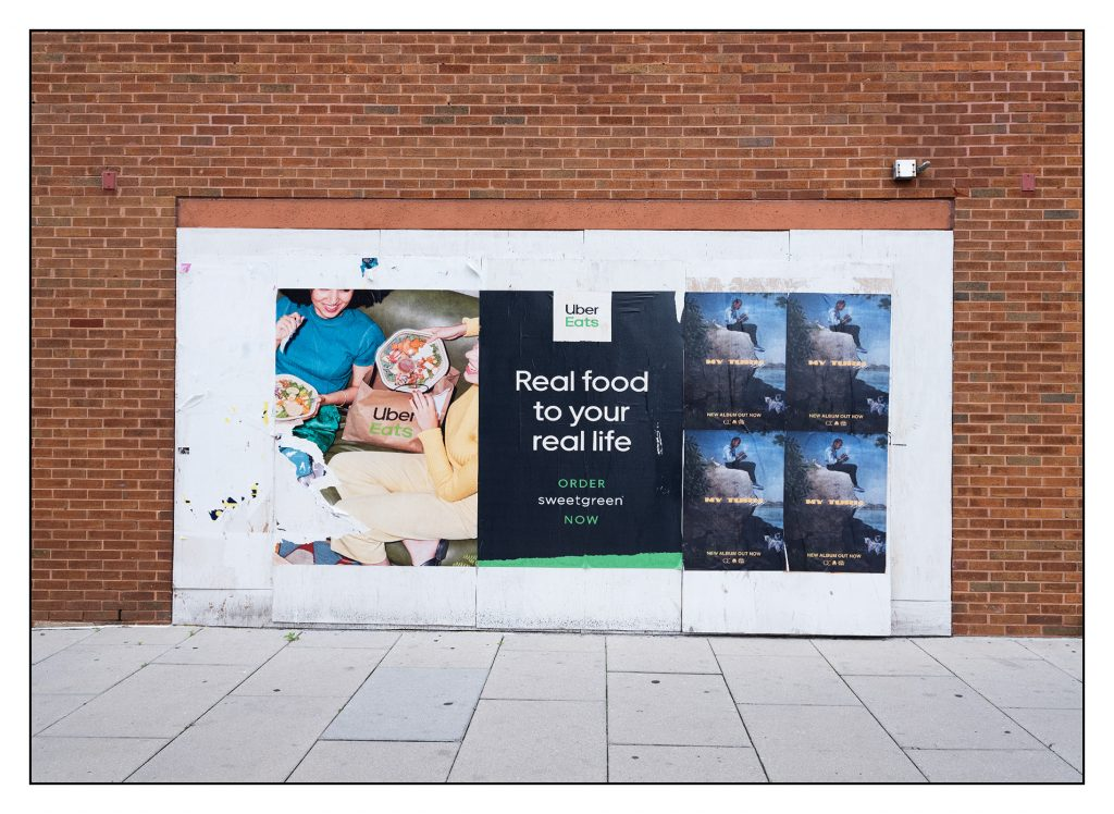"Large poster advertising Uber Eats delivery of Sweetgreen pasted on white painted ply wood covering an opening in a red brick wall.  Slogan ""Real food to your real life"" A quad of smaller posters advertising an album release."