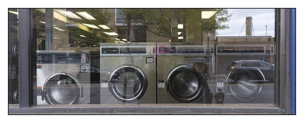 4 commercial graded stainless steel washing machines seen through the window of a closed laundromat. Reflections of the photographer and partner in the window.