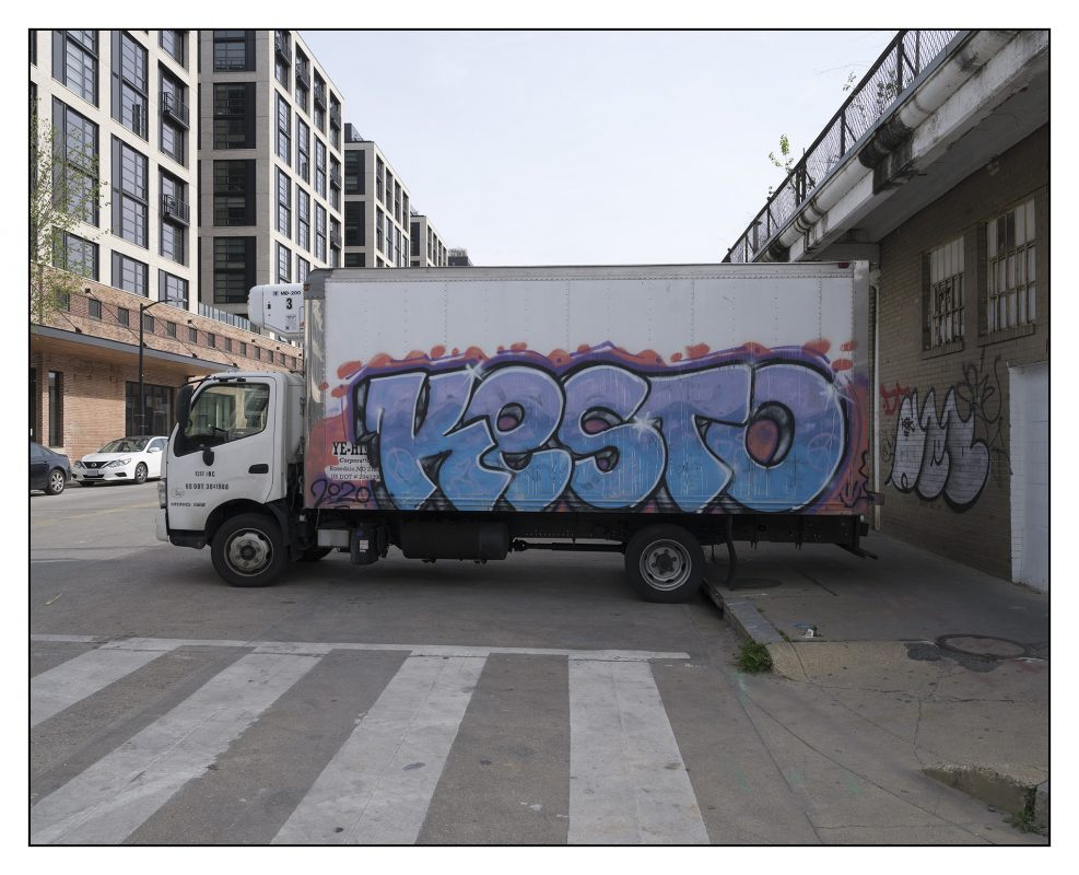 KESTO graffitied onto a while panel truck flanked by receding ranks of new built luxury apartments on the left and a still operating commercial butcher selling goat on the right.