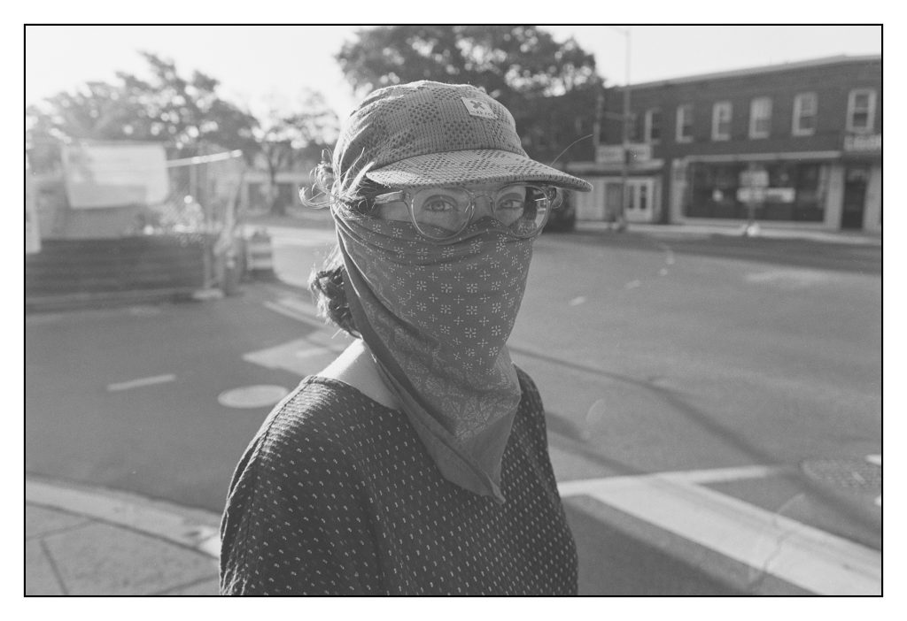 A picture of a woman wearing a mask, hat and shirt each made with fabric of different textures and patterns.